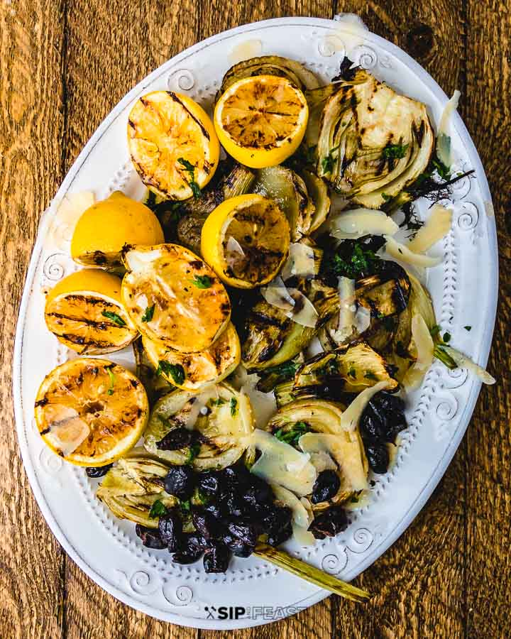 Grilled fennel and lemons with black olives and shaved cheese on white plate on wood table.