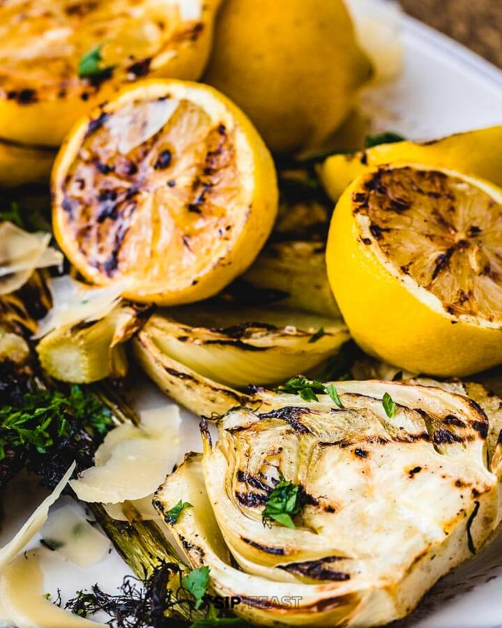 Close up shot of grilled lemons and fennel in white plate.