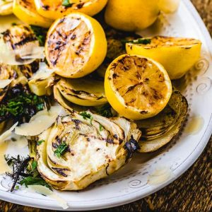 Grilled fennel and grilled lemons on white plate.