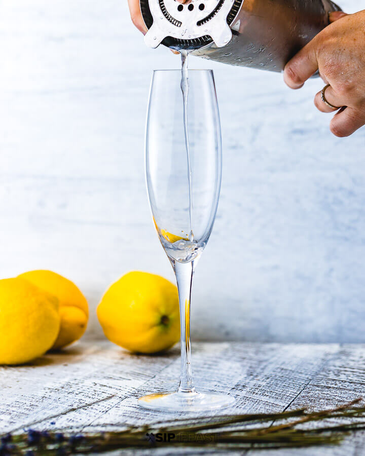 Pouring drink in champagne flute with 3 lemons in background.