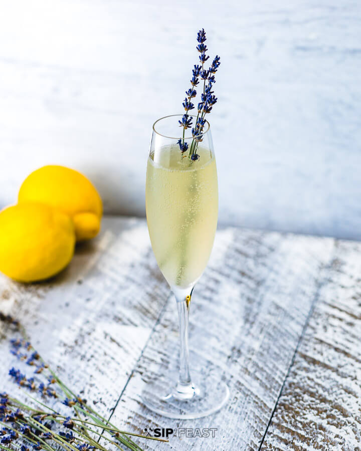 Champagne flute with lavender french 75, fresh lavender and lemons.