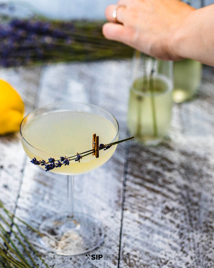 Glass of french 75 with lavender garnish and hands in background arranging more lavender in glasses.