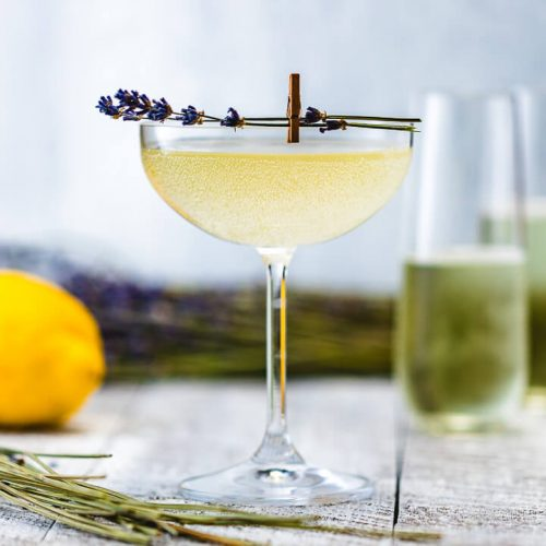 Glass of Lavender French 75 with champagne flutes, lemons and lavender in the background.