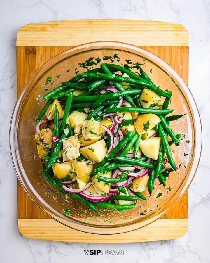 Potato green bean salad in glass bowl on cutting board.