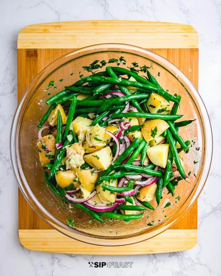 Potato green bean salad in glass bowl on cutting board.
