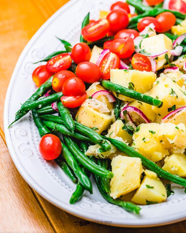 Italian potato green bean salad in platter on wood table.
