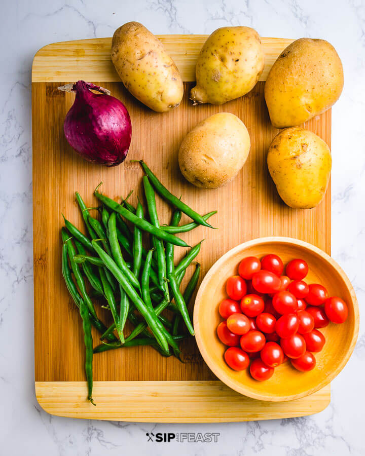 Ingredients show on cutting board: red onion, potatoes, string beans and cherry tomatoes.