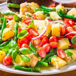 Italian green bean potato salad in platter on blue table.