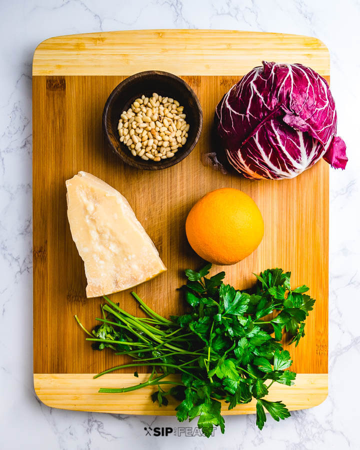 Ingredients shown on cutting board: pine nuts, radicchio, parmigiano reggiano, 1 orange and fresh parsley.