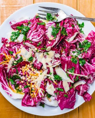 Radicchio salad in white serving dish on wood table.