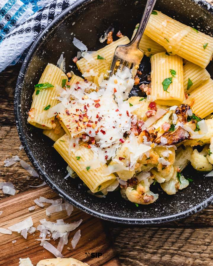Rigatoni with cauliflower and bacon in black bowl on wood table.
