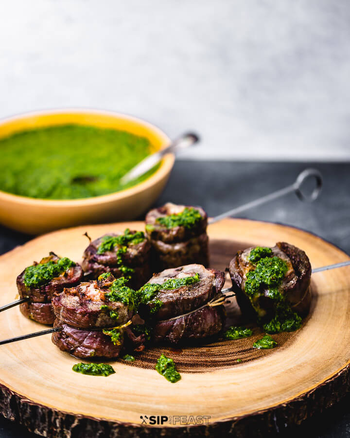 Skewered flank steak pinwheels on cutting board with bowl of green sauce on the side.