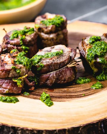 Steak pinwheels on cutting board topped with green sauce.