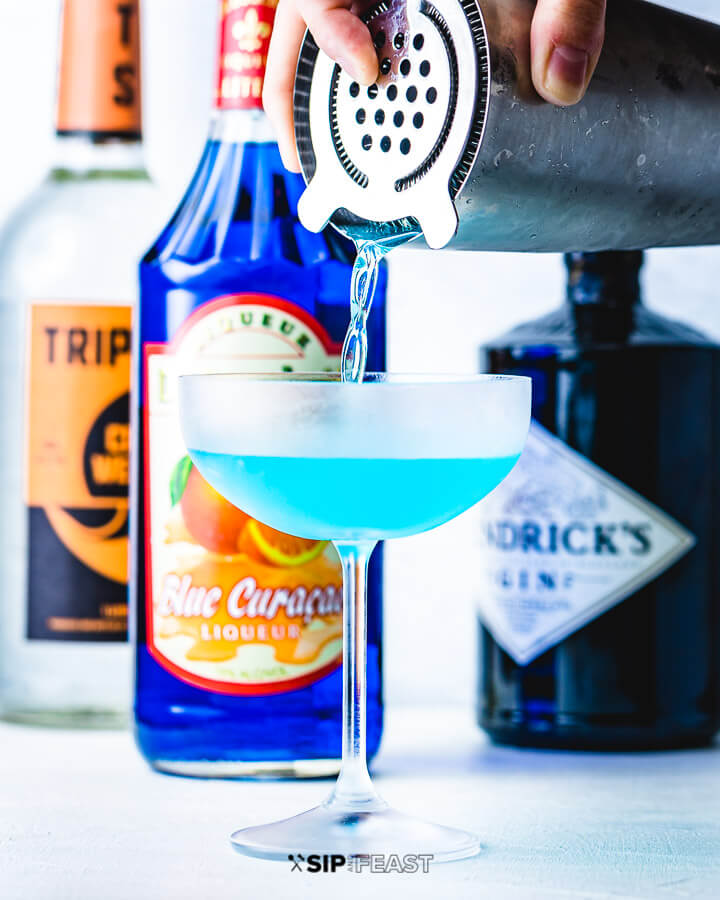 Cocktail shaker contents being poured into a coupe glass with bottles of gin, blue curacao and triple sec in the background.