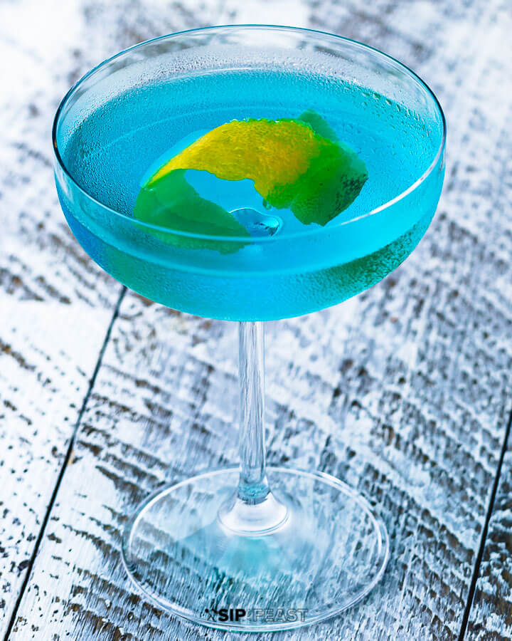 Coupe glass with angelo azzurro cocktail and lemon peel.