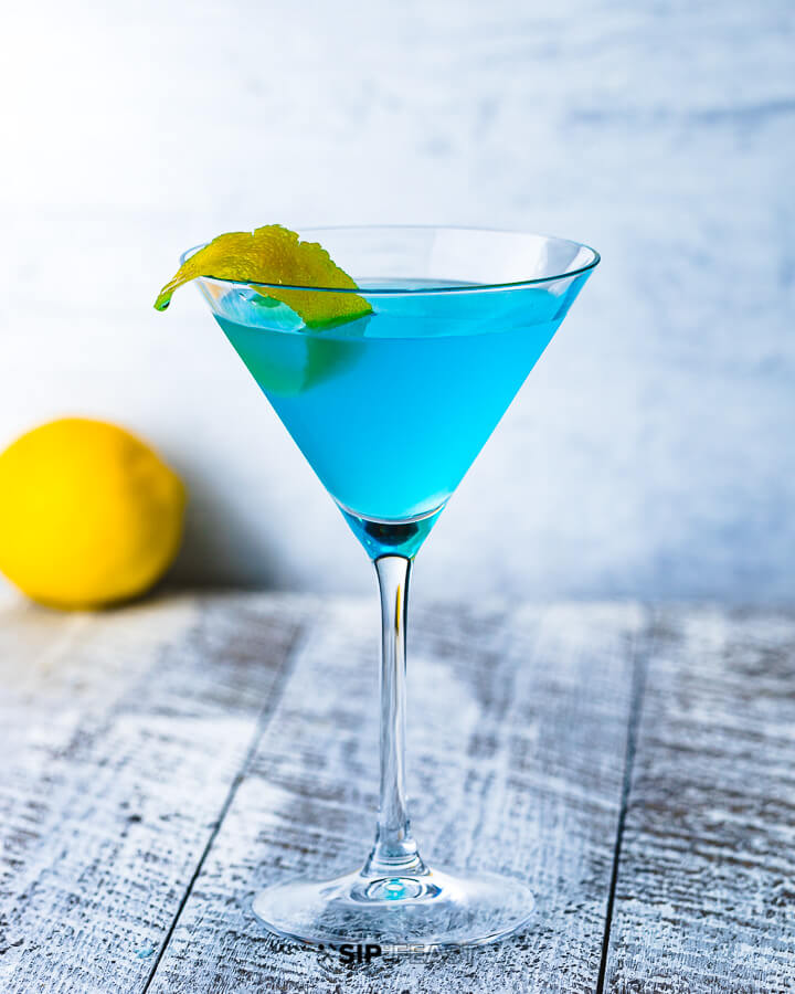 A martini glass with the Angelo Azzuro cocktail and a lemon in the background.