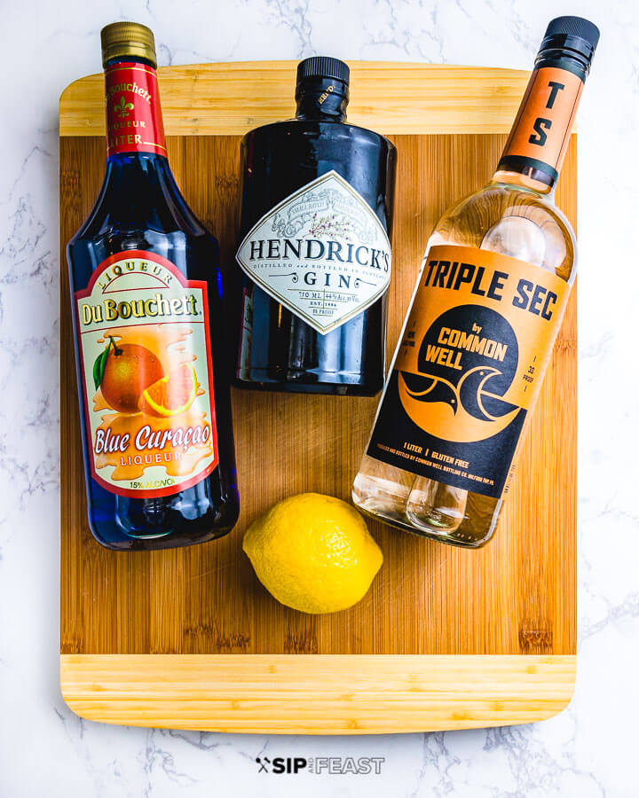 Bottles of blue curacao, gin, triple sec and a lemon on a cutting board.