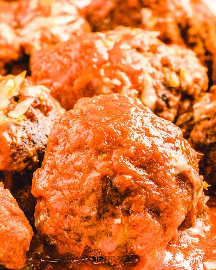 Close up picture of 1 large meatball with sauce.