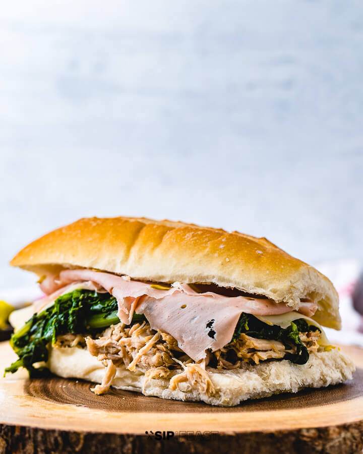 Italian pulled pork sandwich with mortadella on wooden board.