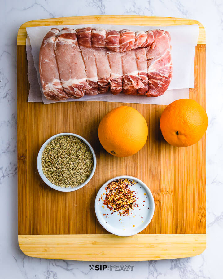 Ingredients shown: pork loin, oranges, bowl of fennel seeds and chili flakes on cutting board.