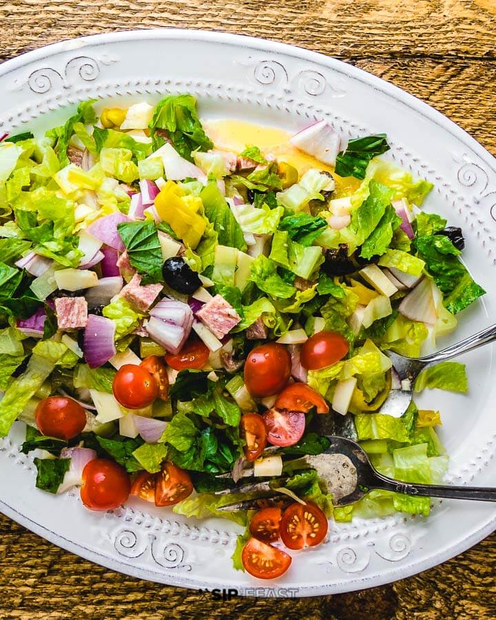 Chopped salad in white plate on wood table.