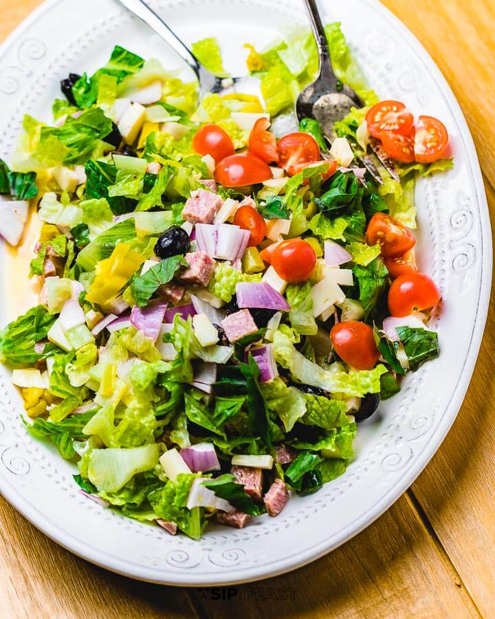 Italian chopped salad in white plate on wood table.
