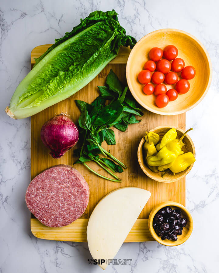 Ingredients shown: romaine lettuce, cherry tomatoes, basil, red onion, salami, provolone, Tuscan peppers and oil cured olives.