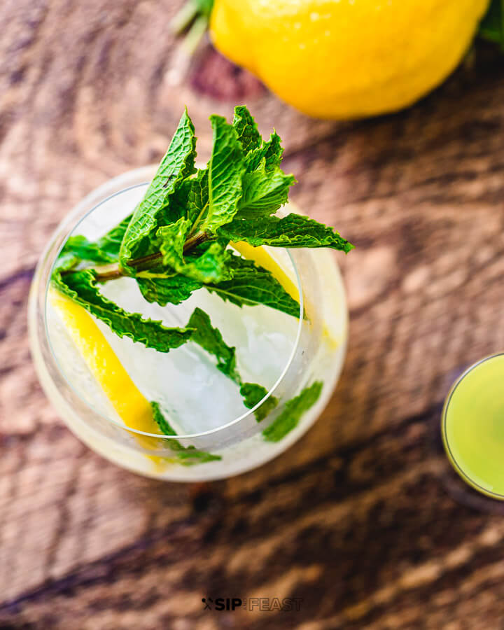 Top down view of a glass of limoncello spritz with mint garnish.