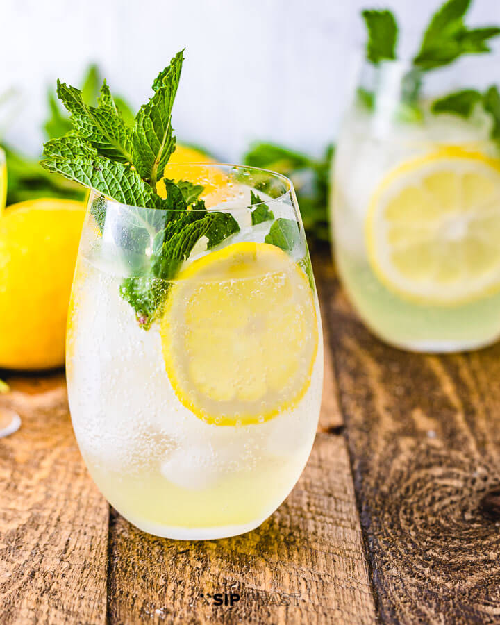 Two glasses of the Limoncello spritz with mint, lemon slices and two lemons in the background.