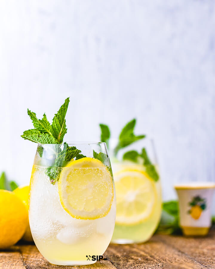 Two glasses of limoncello spritz with mint and lemon and a glass of limoncello in the background.