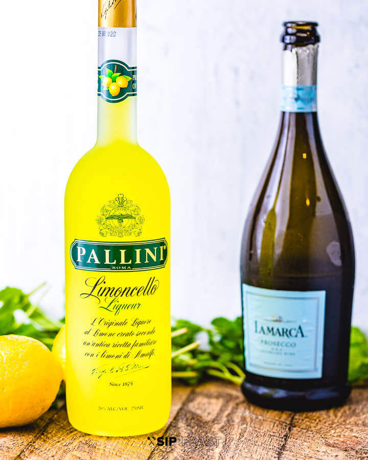 A bottle of limoncello and a bottle of prosecco with lemons and mint in the background.
