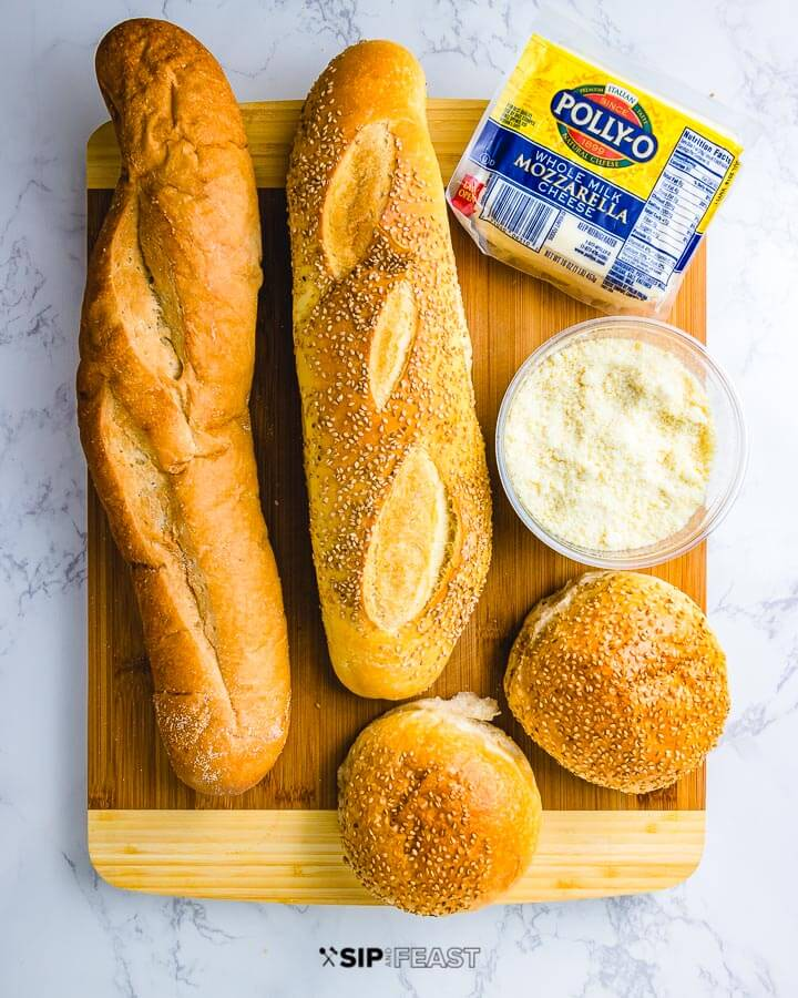 Ingredients shown: 2 loafs Italian bread, 2 seeded rolls, block of mozzarella and parmesan cheese.