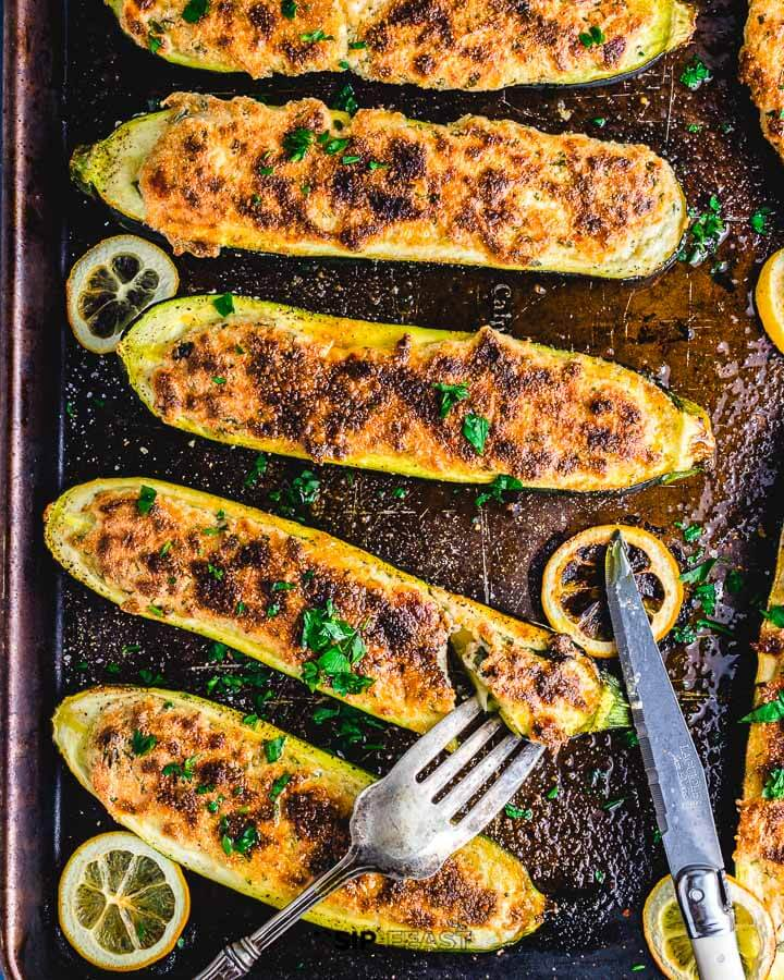 Stuffed zucchini in sheet pan with fork and knife.