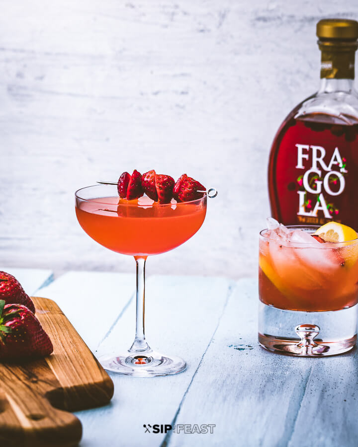 Cutting board with strawberries, two glasses of strawberry lemonade vodka cocktail, and bottle of Fragola liqueur.