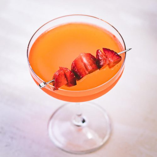 Strawberry lemonade vodka in glass with strawberry garnish.
