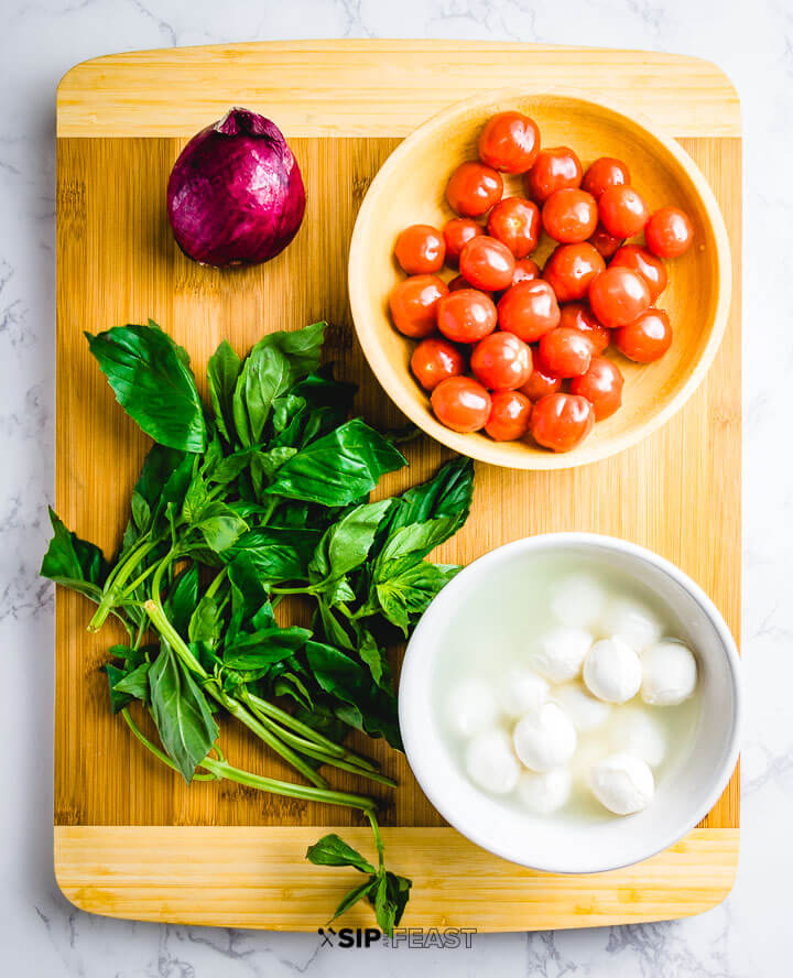 Ingredients on cutting board: red onion, grape tomatoes, basil and a bowl of fresh mozzarella.