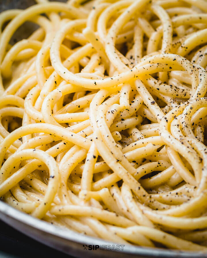 Cacio e pepe in pan with sprinkled pepper.