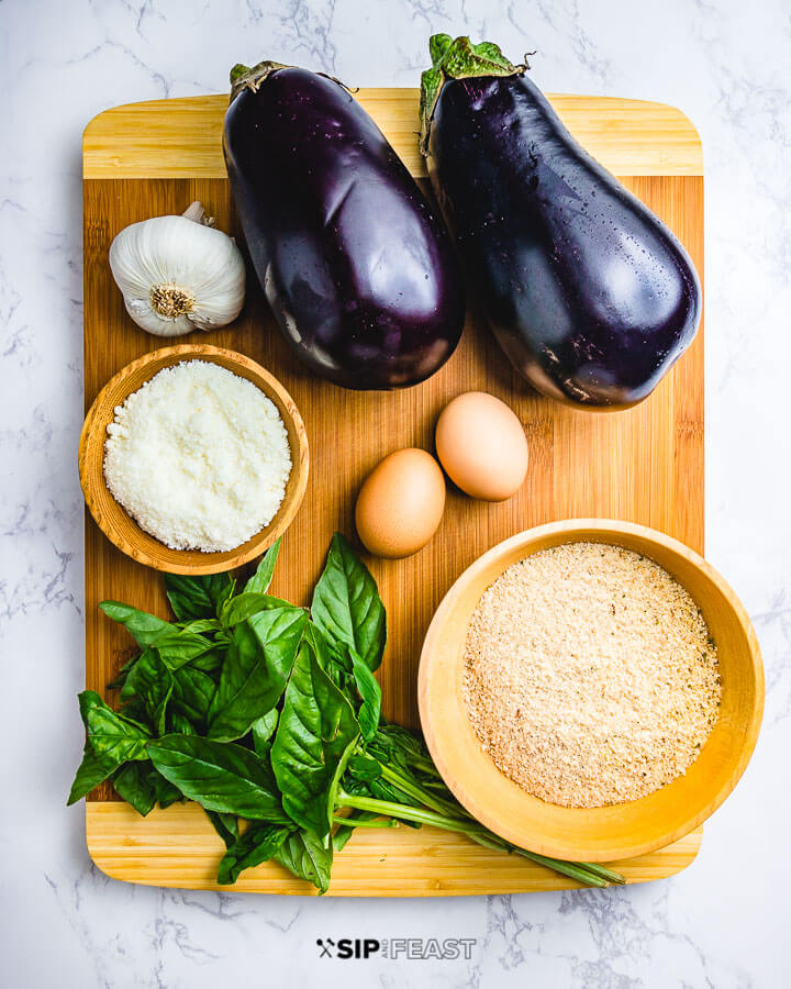 Ingredients shown: garlic, 2 eggplants, Pecorino Romano, 2 eggs, bunch of basil and breadcrumbs.