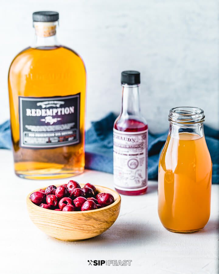 A bottle of rye, cocktail bitters, a bowl of cherries and apple cider.