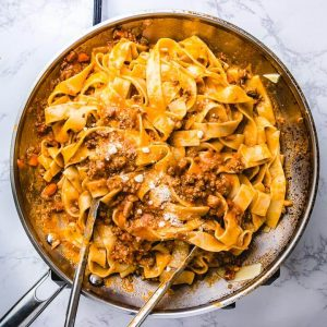 Pappardelle bolognese in large pan with tongs.