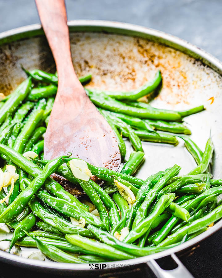 String beans with garlic and oil in pan on blue background.