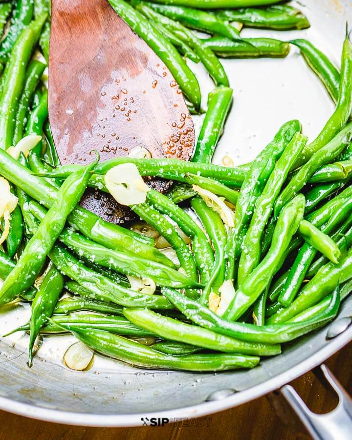 Sauteed garlic string beans in pan with wooden spoon.