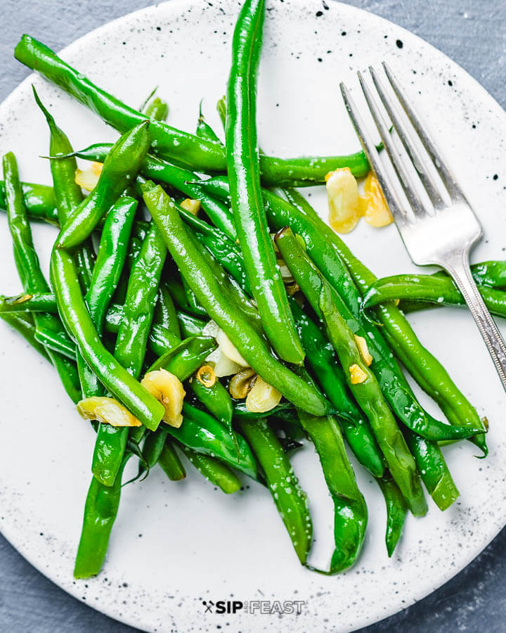 Garlic green beans on white plate.