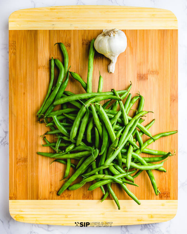 Fresh green beans and garlic head on cutting board.