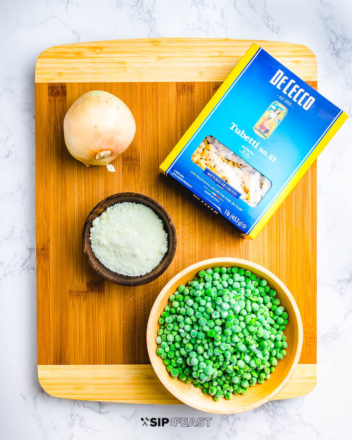 Ingredients on cutting board: 1 onion, box of tubetti pasta, bowl of peas and bowl of grated Parmigiano Reggiano cheese.