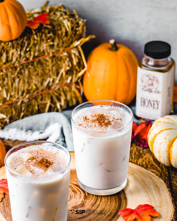 Two glasses of bourbon milk punch with pumpkins , honey, and a hay bale in the background.