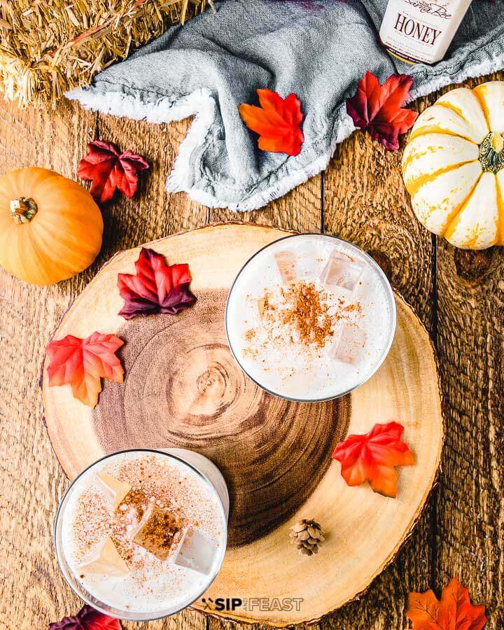 Two glasses with pumpkin spice bourbon milk punch, decorative leaves and pumpkins on a table top.