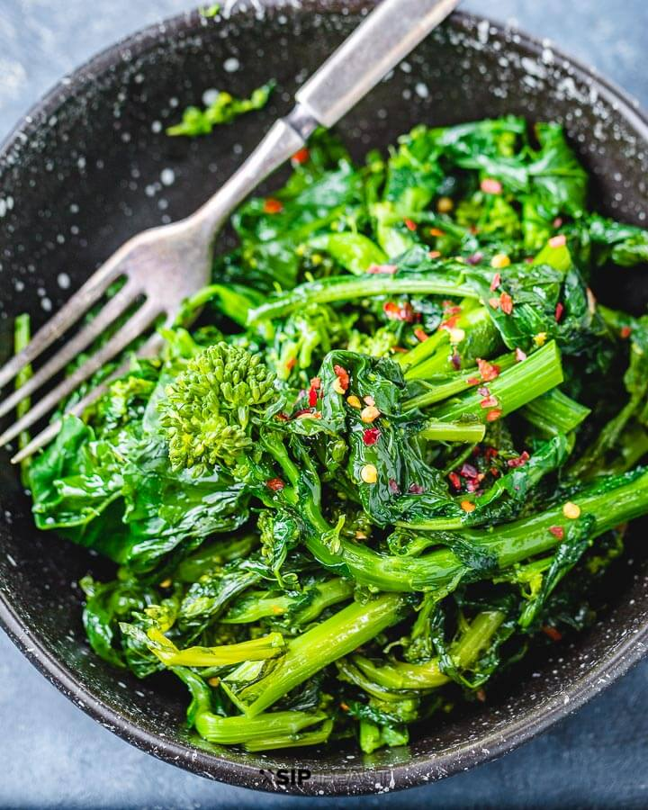 Black bowl with broccoli rabe on blue table.