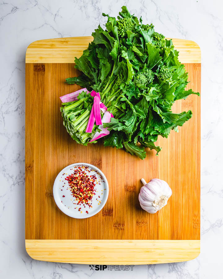 Ingredients on cutting board: One bunch of broccoli rabe, red pepper flakes, and head of garlic.