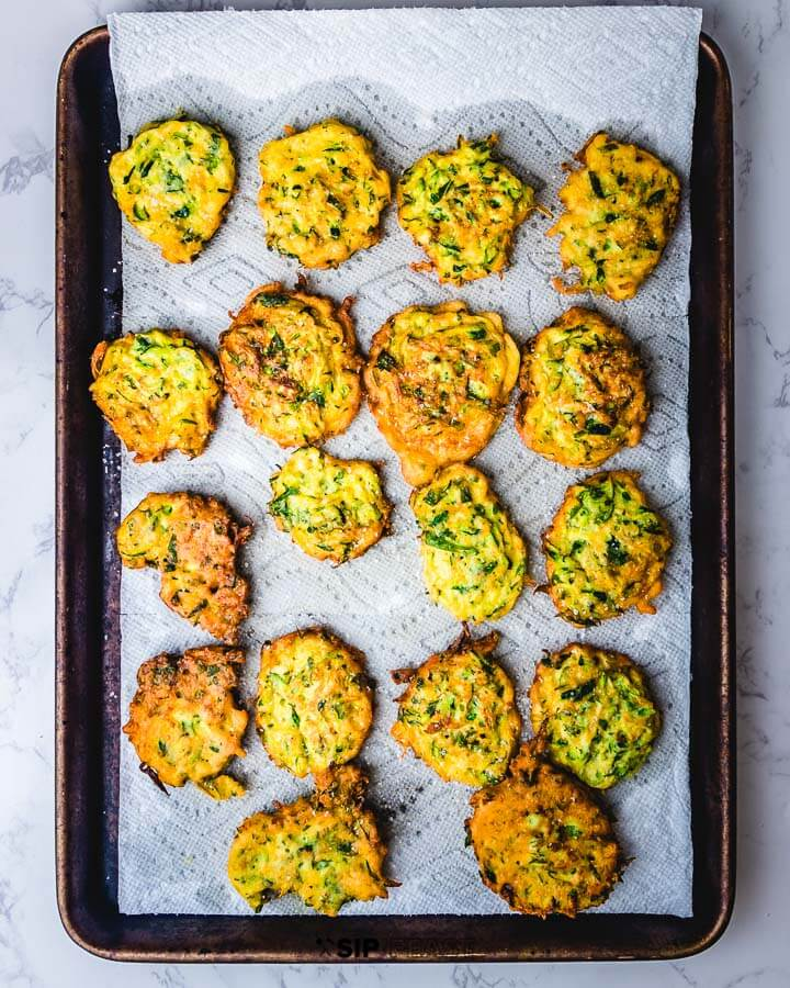Sheet pan of fritters on paper towels.
